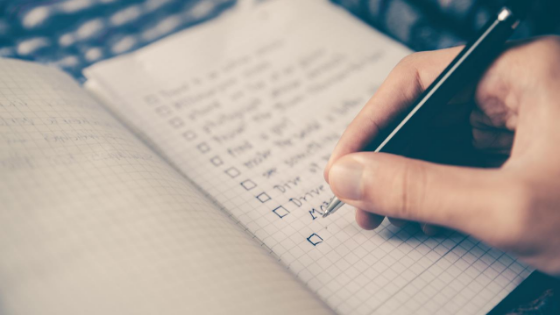 Person ticking off an item on a to-do list written in a notebook